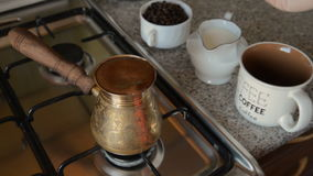 The home coffee in stove. Coffee beans are cooked on the stove. It is stirred with a spoon. In the background in the frame there is a mug and coffee beans in a stock footage