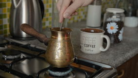 The home coffee in stove. Coffee beans are cooked on the stove. It is stirred with a spoon. In the background in the frame there is a mug and coffee beans in a stock video
