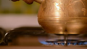 The home coffee in stove. The cezve turk stands and cooks on the stove. The home stove has gas. The cezve turk is made of copper and brass. The camera moves stock footage