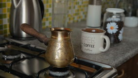 The home coffee in stove. Coffee grain was ground in an electric mill and poured into a cerve turk. Now pour water into it. In the background in the frame there stock video footage
