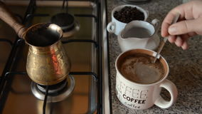 The home coffee in stove. The coffee was cooked on the stove and poured into a mug. Now add milk to it. In the background, there is a coffee in the jar. All stock footage