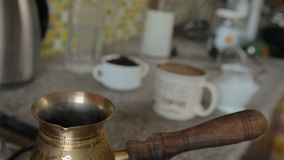 The home coffee in stove. The coffee was cooked on the stove and some of it was poured into a mug. Now from the Turks there is steam or smoke. In the background stock video