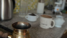 The home coffee in stove. The coffee was cooked on the stove and some of it was poured into a mug. Now from the Turks there is steam or smoke. In the background stock video footage