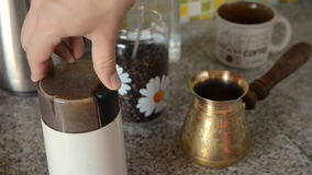 The home coffee in table. Milk coffee in an electric mill. In the background there is a mug for coffee and a cezve turk in the frame. All this is on the table stock footage