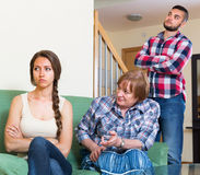 Home conflict at young family with mother. Young couple having quarrel with mature mother at home. Selective focus Stock Photos