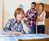 Home conflict at young family with mother. Home conflict between young family with elderly mother. Selective focus Stock Photos