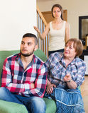 Home conflict at young family with mother. Young family having conflict with elderly mother at home. Selective focus Royalty Free Stock Photos