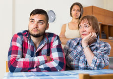 Home conflict at young family with mother. Young family having quarrels with elderly mother at home. Selective focus Royalty Free Stock Photo