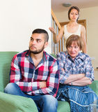 Home conflict at young family with mother. Young married couple with elderly mother having conflict at home. Selective focus Royalty Free Stock Photography