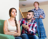 Home conflict at young family with mother. Young married couple having conflict with elderly mother at home. Selective focus Stock Image