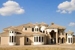 Home Construction. A huge sand colored mansion under construction Royalty Free Stock Photo