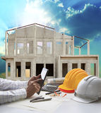 Home construction and hand hold tablet on engineer working table Royalty Free Stock Photography