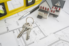 Home, Construction Level, Pencil and Keys Resting on House Plans Stock Photos