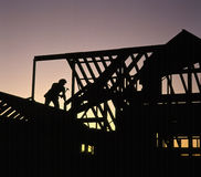 Home Construction Worker. Silhoutte of worker framing a house at sunset Royalty Free Stock Photos
