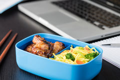 Home cook bento box during office lunch with computer laptop. Chicken wings and noodles in bento box at office lunch Stock Photo