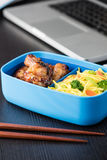 Home cook bento box during office lunch with computer laptop. Chicken wings and noodles in bento box at office lunch Royalty Free Stock Image