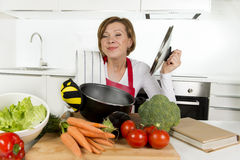 Home cook woman in red apron at domestic kitchen holding cooking pot with hot soup smelling vegetable stew Royalty Free Stock Photos