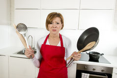 Home cook woman in red apron at domestic kitchen holding pan and household in stress Royalty Free Stock Photo