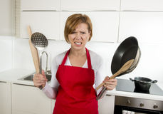 Home cook woman in red apron at domestic kitchen holding pan and household in stress Stock Photography