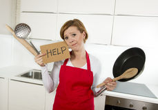 Home cook woman in red apron at domestic kitchen holding pan and household in stress Stock Images