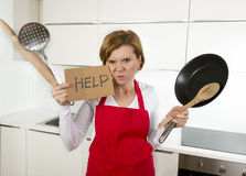 Home cook woman in red apron at domestic kitchen holding pan and household in stress Stock Image