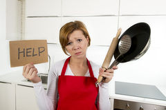 Home cook woman in red apron at domestic kitchen holding pan and household in stress Royalty Free Stock Photography