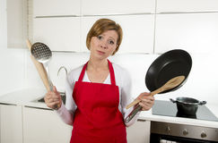 Home cook woman in red apron at domestic kitchen holding pan and household in stress Royalty Free Stock Image