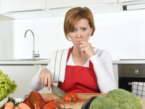 Home cook woman in red apron slicing carrot with kitchen knife suffering domestic accident cutting hurting finger Royalty Free Stock Image
