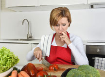 Home cook woman in red apron slicing carrot with kitchen knife suffering domestic accident cutting hurting finger Royalty Free Stock Photography