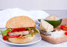 Home cooked burger with turkey, avocado, lettuce, onions, red paprika pepper on a sesame seed bun. Royalty Free Stock Photography