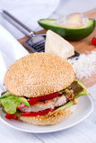 Home cooked burger with turkey, avocado, lettuce, onions, red paprika pepper on a sesame seed bun. Stock Photo