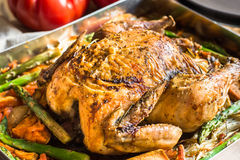 Home cooked roasted chicken with vegetables carrots, sweet potatoes, asparagus in baking form, tomatoes. Kitchen table, closeup Royalty Free Stock Images