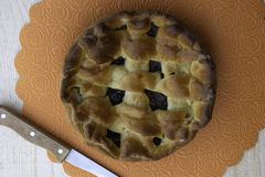 Apple jam pie filled with cherries and walnuts and a knife lying on a wooden table stock photos