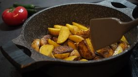 Home cooking background. Fatty food. Appetizing rustic yellow unpeeled potatoes cooked with olive oil fried in a pan. Stir with a spatula and cover with a lid stock footage