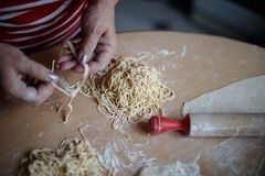 Home cooking noodles. In the kitchen with her grandmother Stock Photography