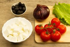 Home cooking summer Greek salad on wooden background Stock Photos