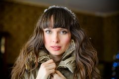 Home cosiness. Beautiful surprised fashionable woman at home in a winter jacket with jewelery on her head. portrait of a woman Stock Photo