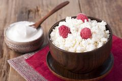 Cottage cheese with raspberry in wooden bowl. Home cottage cheese with raspberry in wooden bowl on old wooden table Stock Photo