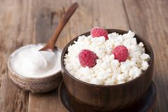 Cottage cheese with raspberry in wooden bowl. Home cottage cheese with raspberry in wooden bowl on old wooden table Stock Image
