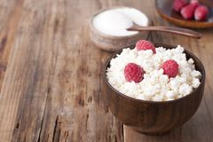 Cottage cheese with raspberry in wooden bowl. Home cottage cheese with raspberry in wooden bowl on old wooden table Royalty Free Stock Photography