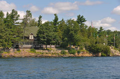 Home Cottage in Thousand Islands with American Flag Royalty Free Stock Images