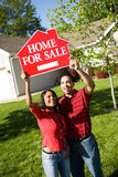 Home: Couple Holds Up For Sale Sign. Extensive series of a Caucasian Real Estate Agent and African-American Couple in front of a home Stock Images