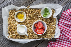 Home crispy golden granola mixture of flakes and nuts on a baking sheet from the oven with yogurt and fresh berries. The. Concept of pure healthy organic food Royalty Free Stock Images
