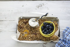 Home crispy golden granola mixture of flakes and nuts. On a baking sheet from the oven with yogurt and fresh blueberries. The concept of pure healthy organic Stock Photo