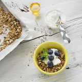 Home crispy golden granola mixture of flakes and nuts. On a baking sheet from the oven with yogurt and fresh blueberries. The concept of pure healthy organic Stock Photos