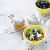 Home crispy golden granola mixture of flakes and nuts. On a baking sheet from the oven with yogurt and fresh blueberries. The concept of pure healthy organic Stock Image