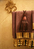 Home Decor. Luxurious purple and gold bathroom towels on a gold towel rack Stock Photos