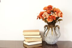 Home Decor. Vase of silk flowers next to stack of old hardback books Stock Image