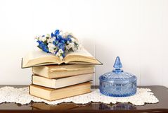 Home Decor. Arrangement with books, crystal dish, silk flowers and antique doily Stock Photos