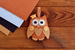 Home decor cute toy on wooden background. Felt owl sewing pattern. Soft owl embellishment or ornament. Brown, white, beige and black felt sheets. Crafts sewing Royalty Free Stock Photos